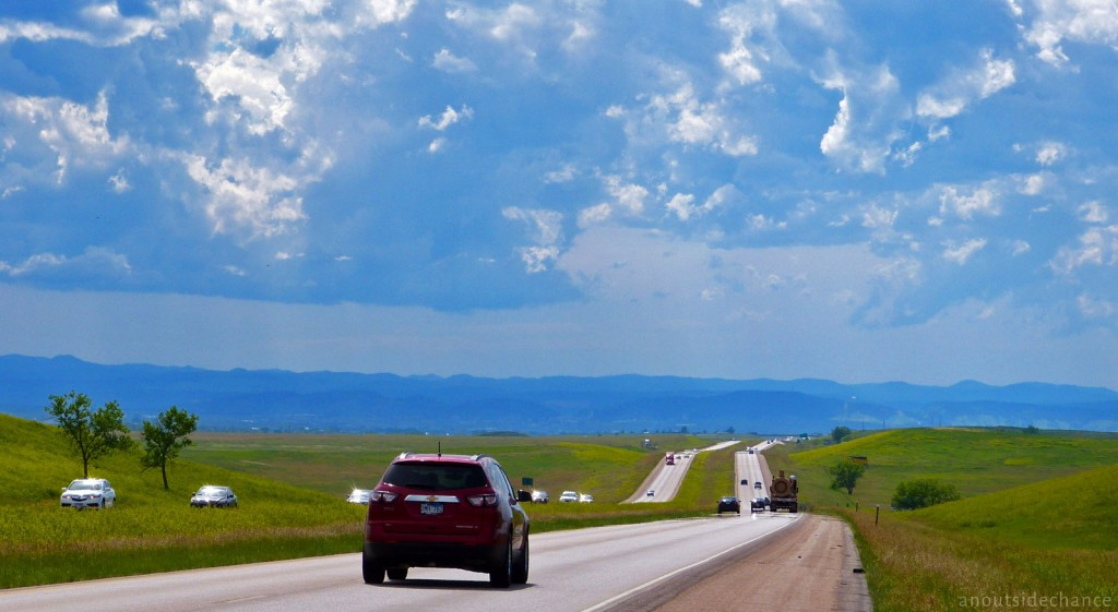 Interstate 90 between Wall and Rapid City, South Dakota, with the Black Hills looming in the background. Cyclists are allowed on Interstate highways in both Dakotas. The traffic makes for a noisy ride, but the wide paved shoulders make for a comfortable ride. On this day I also chose I-90 because the bridge overpasses would offer some shelter if I didn't beat the predicted late-afternoon hailstorm. June 21, 2014.
